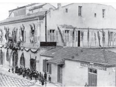 Το κτίριο του «Αγίου Ανδρέα», εδώ η πλευρά προς τη Μαιζώνος. ∆εξιά, προς τη Βούρβαχη, το μαγαζί αδελφών Ιωάννου, σήμερα βρίσκεται διαγωνίως απέναντι, Μαιζώνος και Αράτου. Η φωτογραφία προέρχεται από το βιβλίο «Οι Μαριανοί Αδελφοί στην Ελλάδα 1907-2007», Ε
