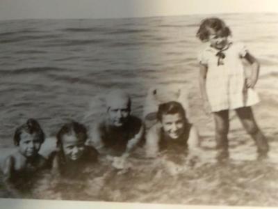 Τέλη της δεκαετίας του '30.Η μικρή Ευγενούλα, όρθια, με φιλους και συγγενείς στη θάλασσα στο Αίγιο /Αρχείο οικογένειας Καζάκου